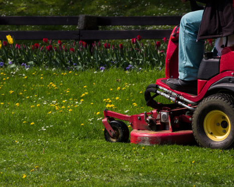 Ma mowing lawn on commercial riding mower